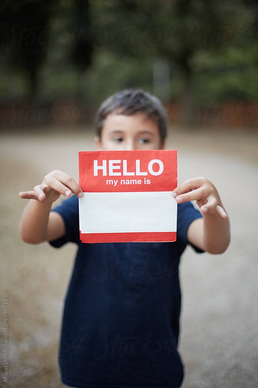 Young child holding  a napkin with the words hello my name is by Miquel Llonch for Stocksy United