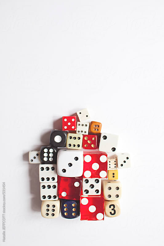 a collection of vintage dice arranged in the shape of a house on a white background by Natalie JEFFCOTT for Stocksy United