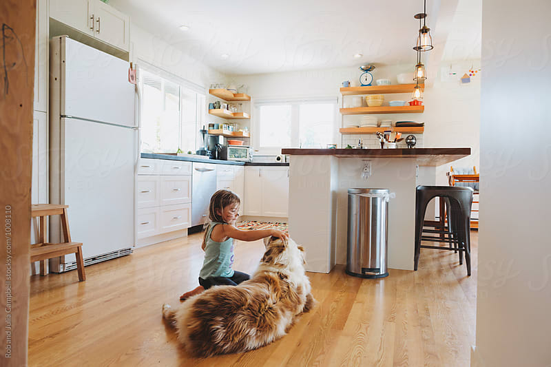 Little girl playing with dog on kitchen floor by Rob and Julia Campbell for Stocksy United