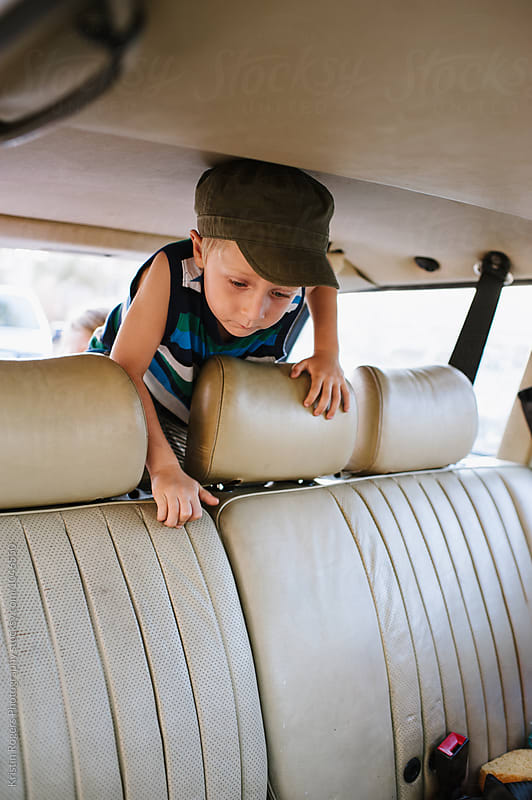 young boy with hat climbing over backseat in car by Kristin Rogers Photography for Stocksy United