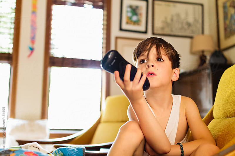 boy holding remote watching tv by Jess Lewis for Stocksy United