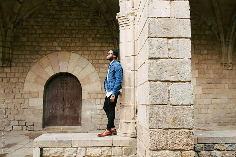Side view of a guy standing in old town. by BONNINSTUDIO for Stocksy United