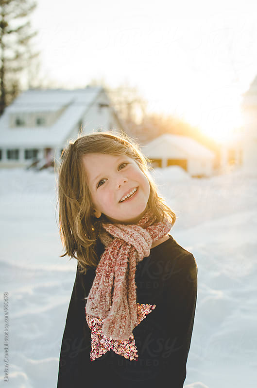Smiling child outside in winter by Lindsay Crandall for Stocksy United