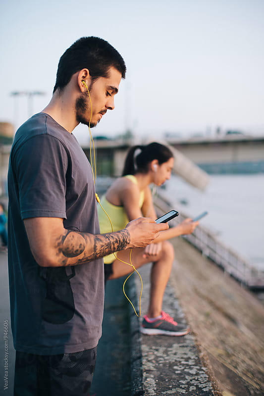 Man in sportswear using his smart phone outdoors by VeaVea for Stocksy United