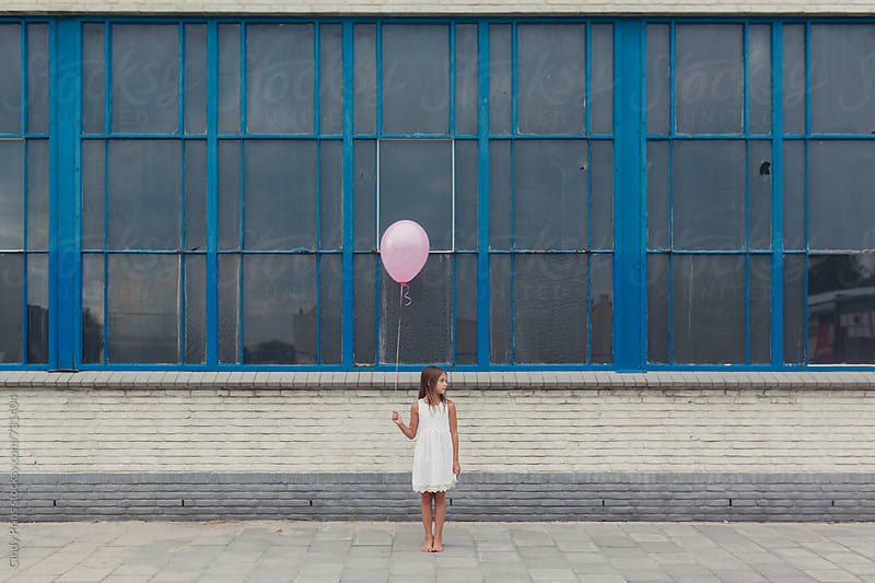 Barefoot little girl in white dress with pink balloon in front of old building by Cindy Prins for Stocksy United
