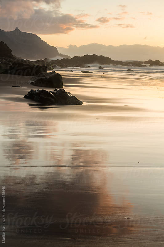 Hazy sunset and low tide on a beach of black sand by Marilar Irastorza for Stocksy United