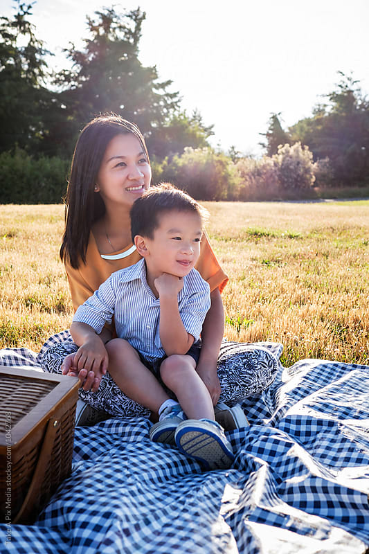 Portrait of Asian mother and her child having picnic outdoor in a park by Suprijono Suharjoto for Stocksy United