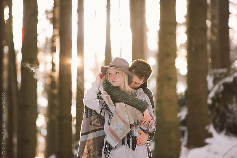 Lovely couple in the snowy woods by Török-Bognár Renáta for Stocksy United