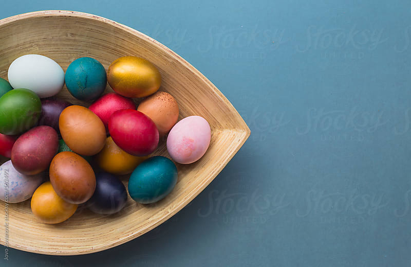 Bunch of colorful Easter eggs in wooden plate by Jovo Jovanovic for Stocksy United