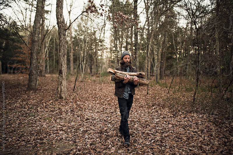 Man gathering fire wood by Isaiah & Taylor Photography for Stocksy United