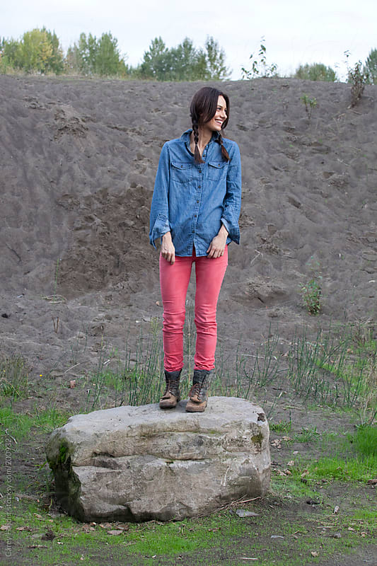 A Female Standing On A Rock Laughing by Carey Haider for Stocksy United