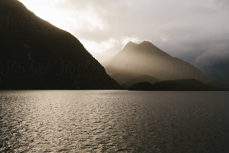 ray of light against dark mountain on fjord by Cameron Zegers for Stocksy United