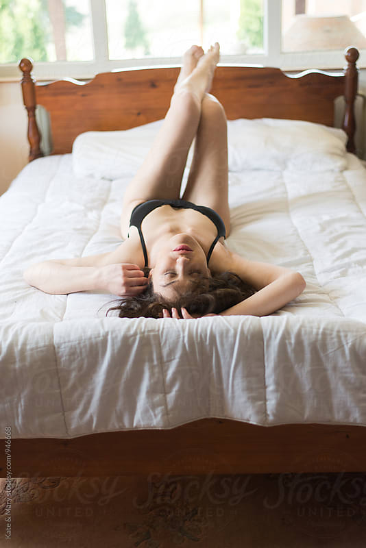 Portrait of sexy woman lay in bed by Kate & Mary for Stocksy United