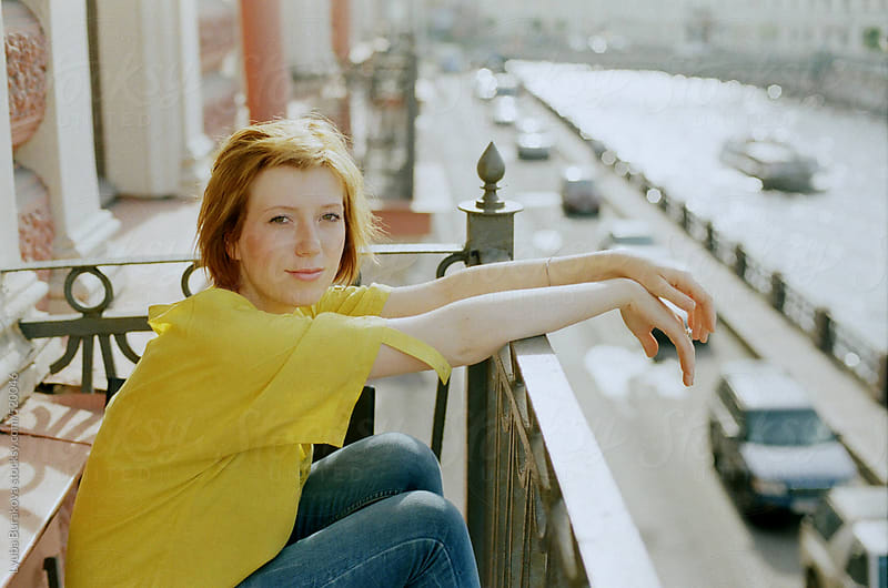 Beautiful young woman sitting on the balcony and looking at camera by Lyuba Burakova for Stocksy United
