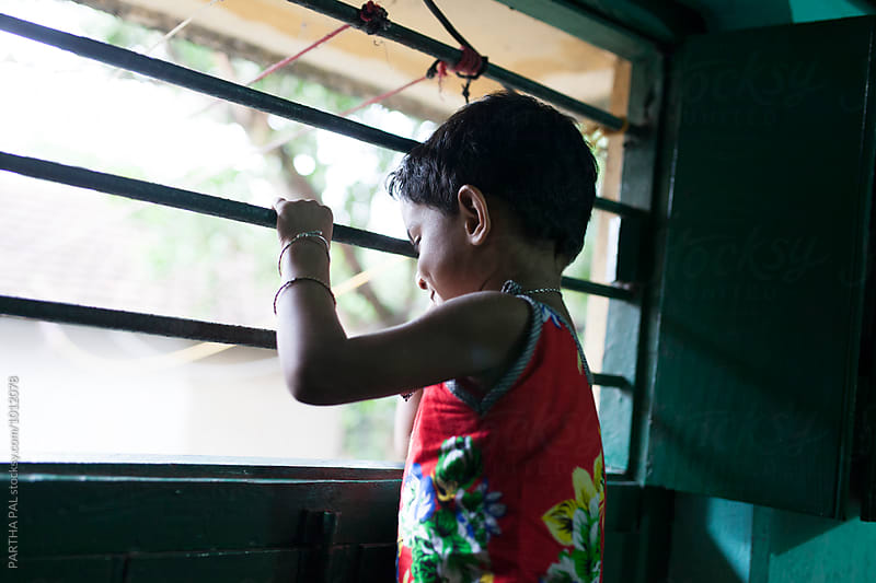 Little girl looking through wndow by PARTHA PAL for Stocksy United