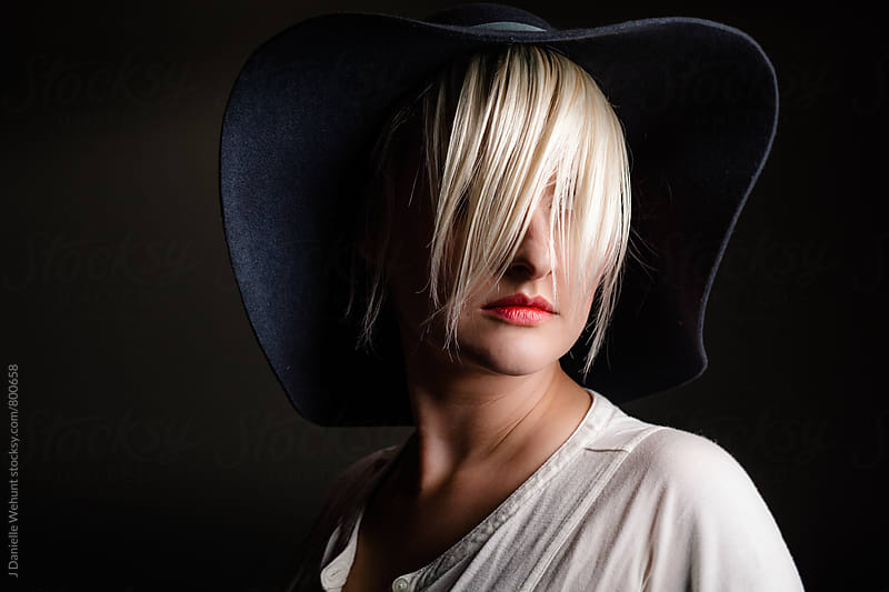 A caucasian woman with short blond hair wearing a hat hiding her face behind her hair. by J Danielle Wehunt for Stocksy United