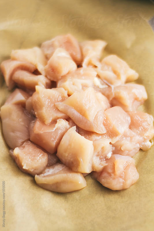 Raw chopped chicken on brown baking paper by Kirsty Begg for Stocksy United