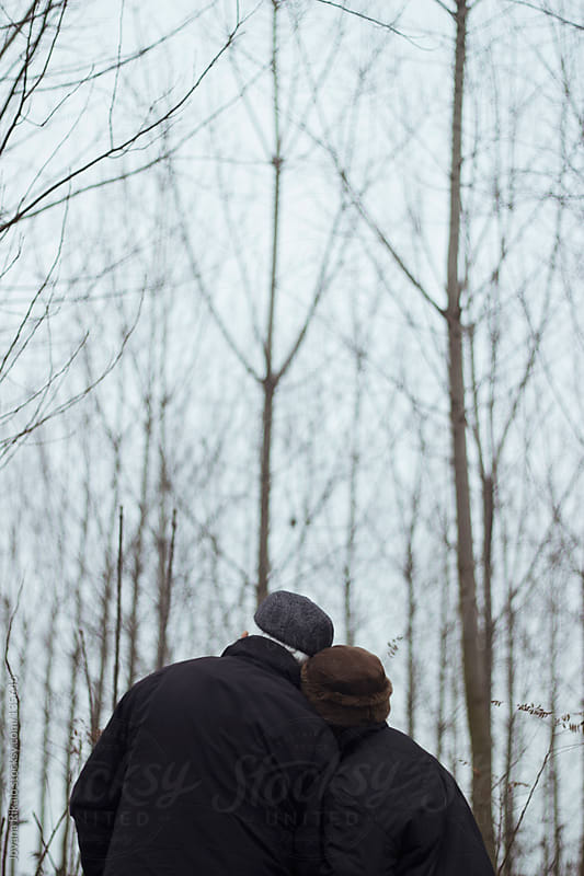 Embraced old couple in love standing in forest by Jovana Rikalo for Stocksy United
