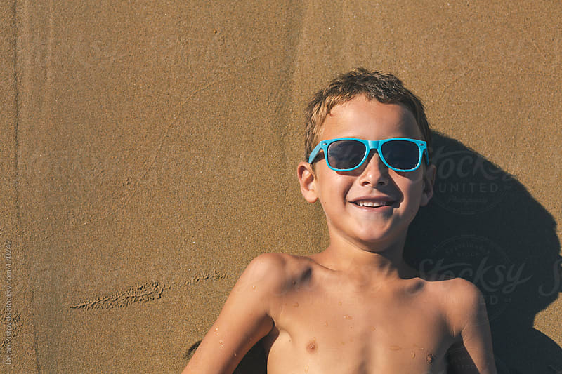 Cheerful child lying on the sand by Dejan Ristovski for Stocksy United