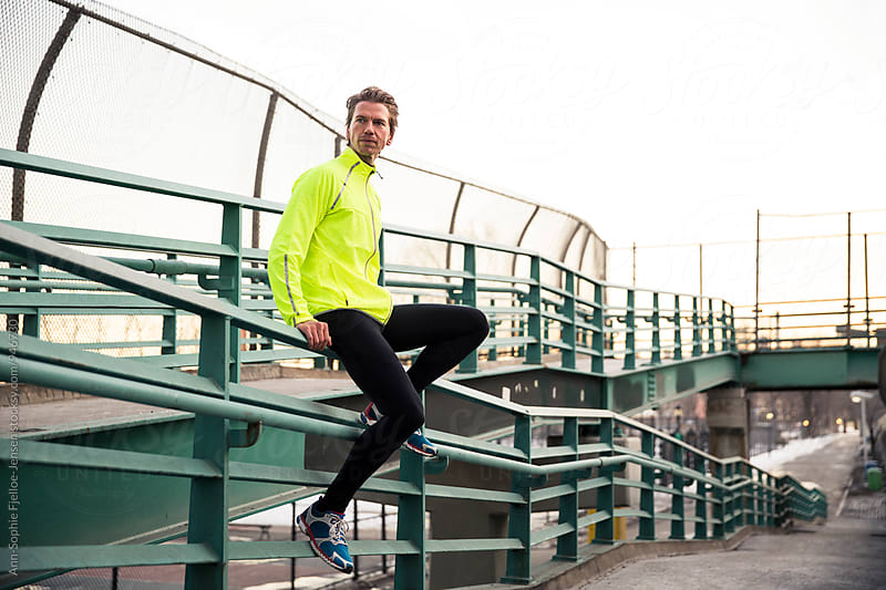 Male runner sitting on a hand rail by Ann-Sophie Fjelloe-Jensen for Stocksy United