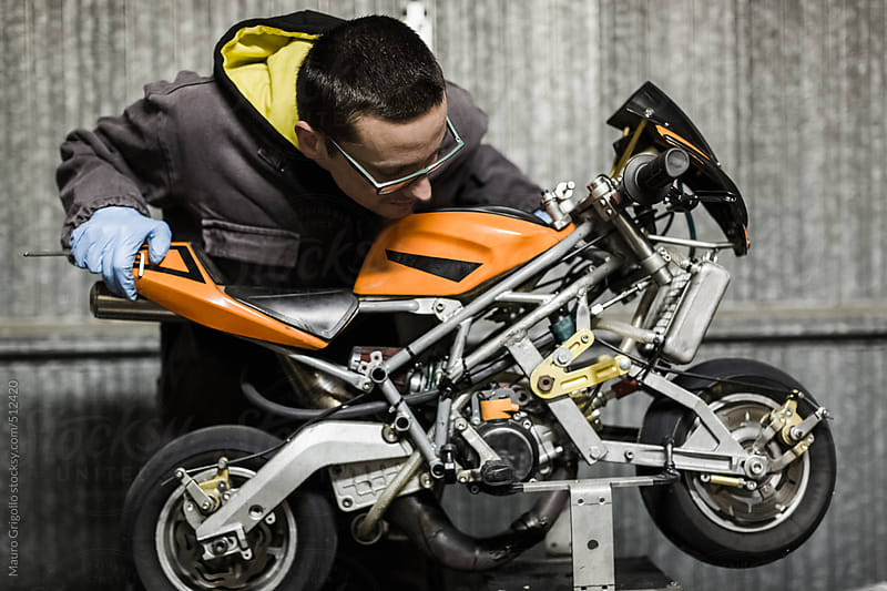 Mechanic works on mini motorbike by Mauro Grigollo for Stocksy United