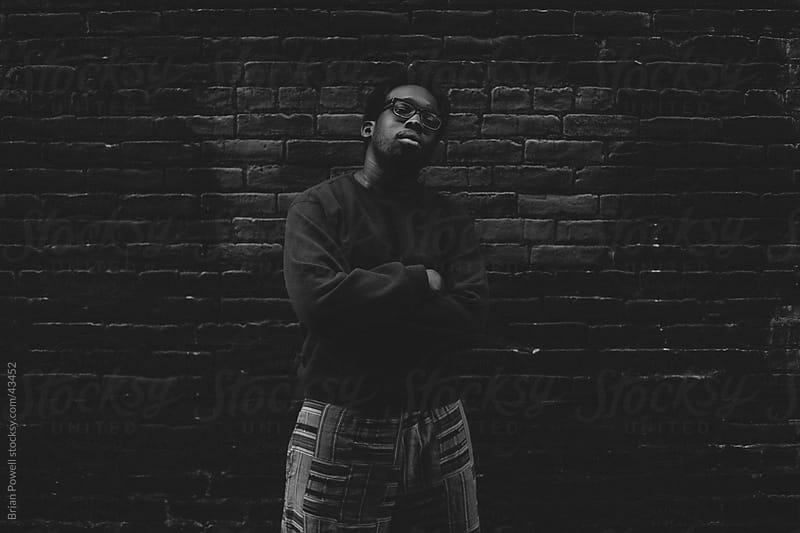 confident youth in dark alley by Brian Powell for Stocksy United