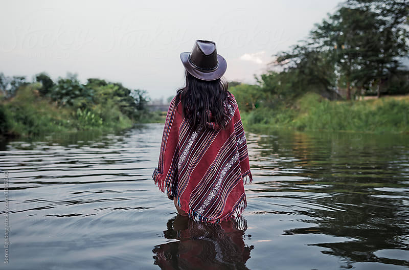 Woman walking in river wearing a red poncho and hat by Soren Egeberg for Stocksy United