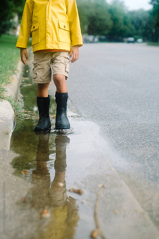 boy in yellow rain jacket stands in puddle by Tara Romasanta for Stocksy United