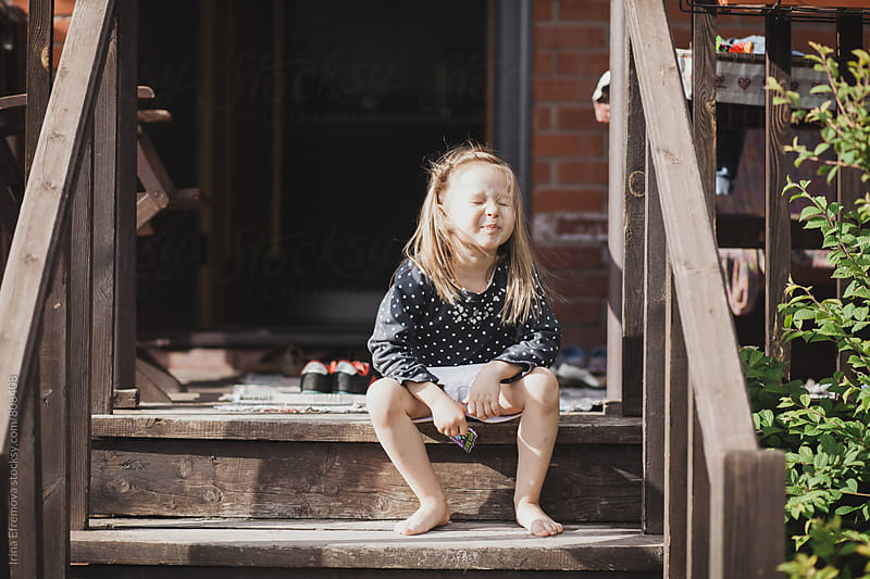Cheeky girl sitting on the porch by Irina Efremova for Stocksy United