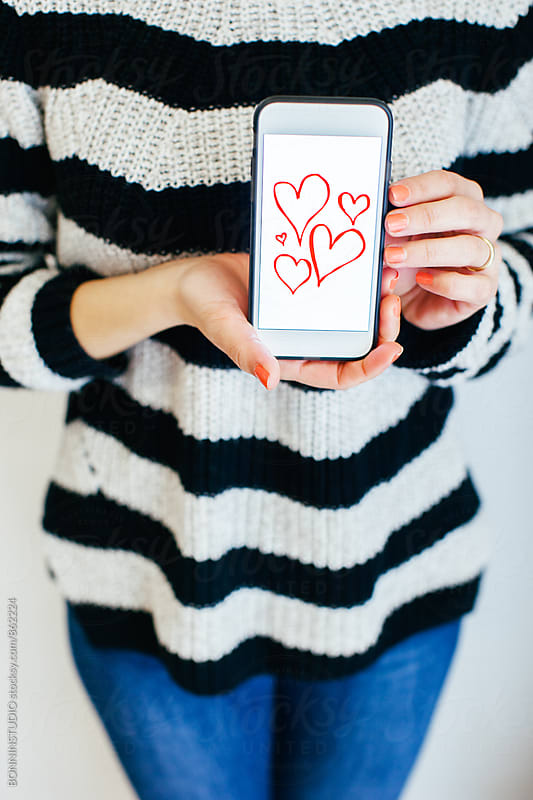 Closeup of a woman showing red hearts painted on phone for Valentine's day. by BONNINSTUDIO for Stocksy United