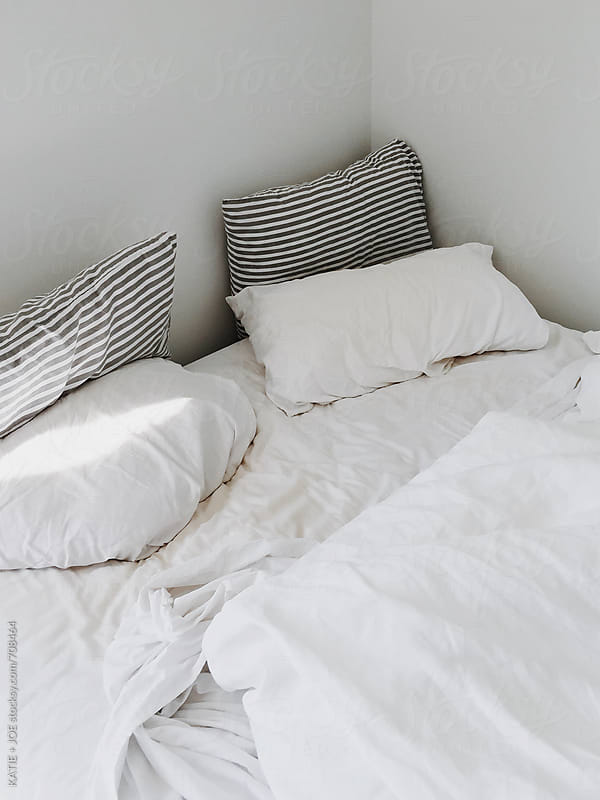 white bed with pillows and a streak of light by KATIE + JOE for Stocksy United