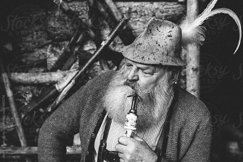 black and white portrait of a typical old austrian bearded man with millinery smoking a pipe by Leander Nardin for Stocksy United