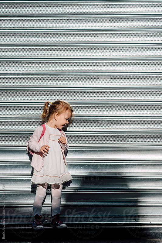 Child standing against the grey garage doors  by Boris Jovanovic for Stocksy United