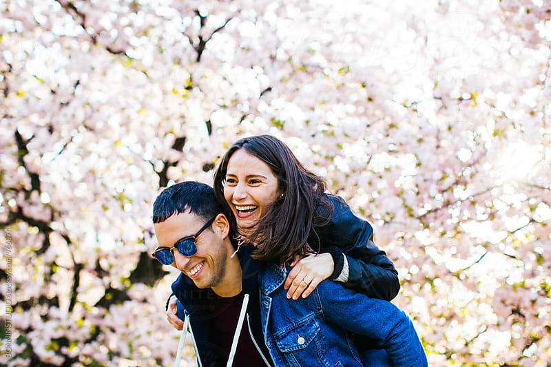 Happy young couple on a piggyback in a park. by BONNINSTUDIO for Stocksy United