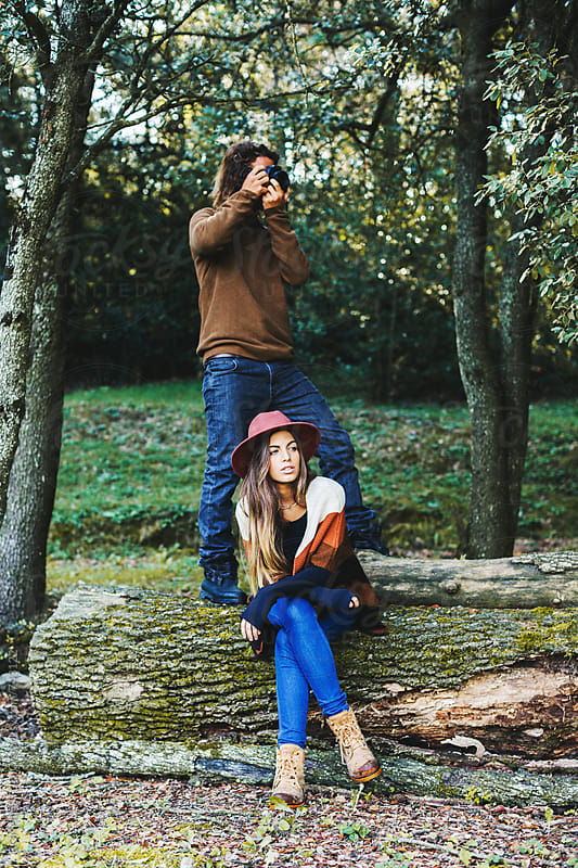 Man taking photos of landscape and woman sitting on a big trunk in the woods. by BONNINSTUDIO for Stocksy United