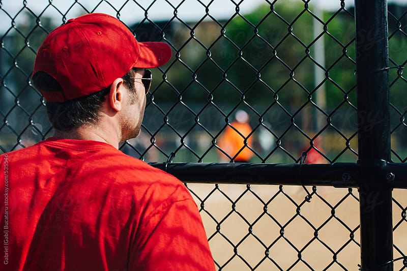 Baseball coach with red shirt and cap watching a game by Gabriel (Gabi) Bucataru for Stocksy United