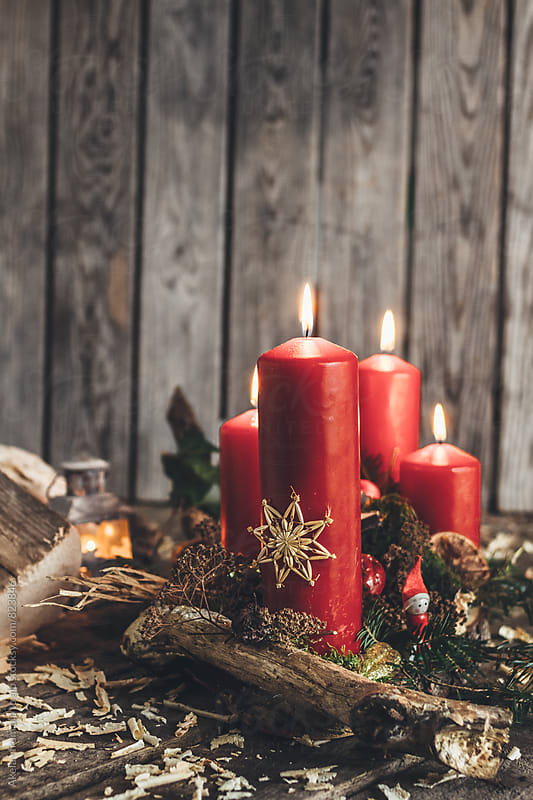 advent wreath with four red burning candles on wooden background by Leander Nardin for Stocksy United
