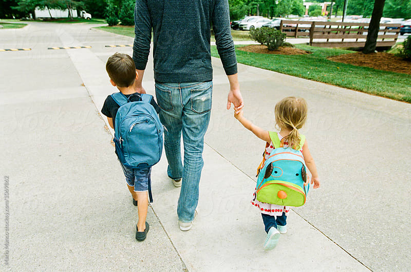 children walk with dad holding hands by Maria Manco for Stocksy United