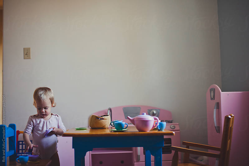 Cute toddler girl having a tea party by Rob and Julia Campbell for Stocksy United