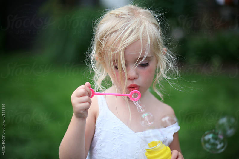Girl Blowing Bubbles by ALICIA BOCK for Stocksy United