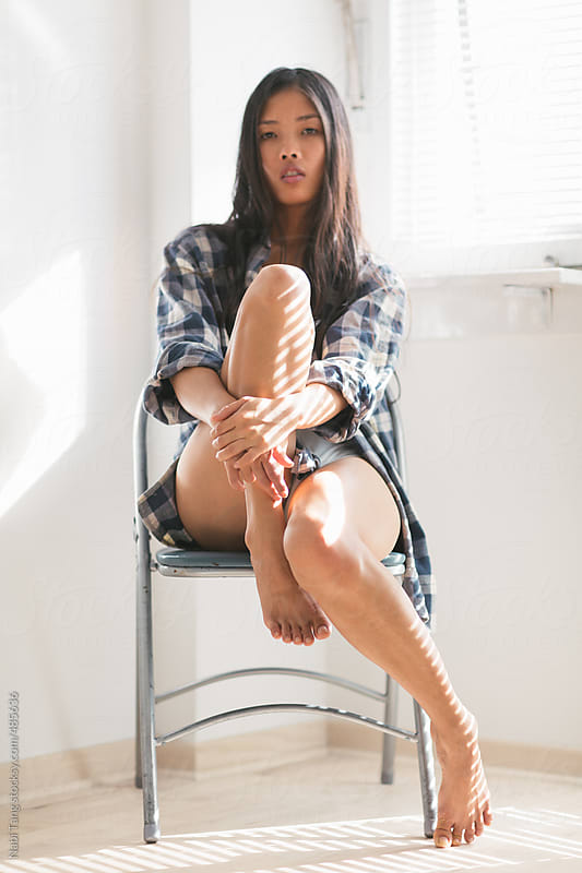 Beautiful young Asian woman sitting on the chair in the white room by the window by Nabi Tang for Stocksy United