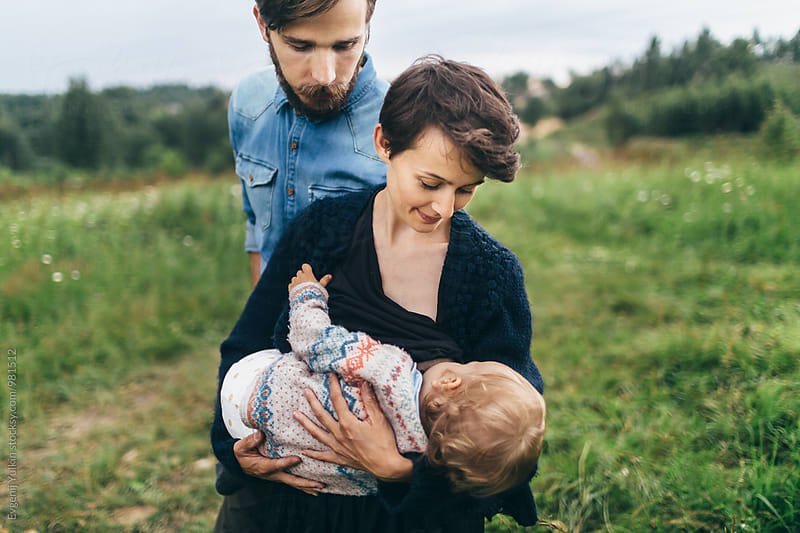 Mother and father looking at their baby girl by Evgenij Yulkin for Stocksy United