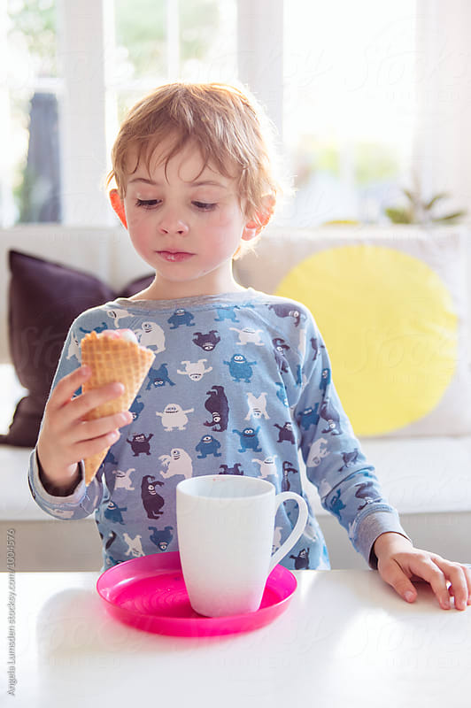Boy wearing pajamas seriously considering the ice cream cone in his hand by Angela Lumsden for Stocksy United