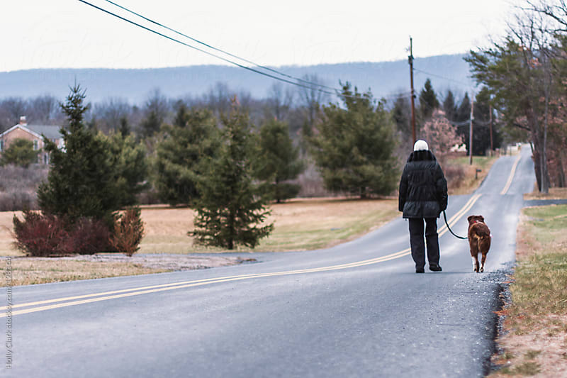 An older woman walks her dog on along a rural road. by Holly Clark for Stocksy United