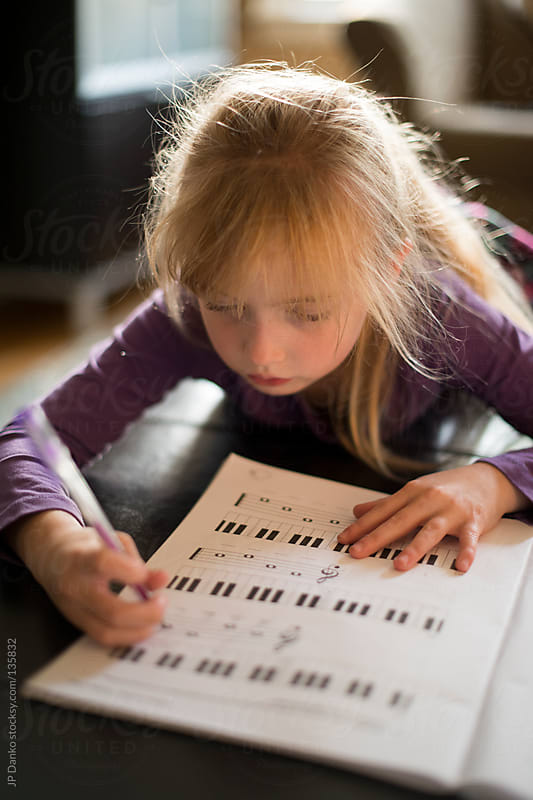 Little Girl Learning to Play Piano with Sheet Music by JP Danko for Stocksy United