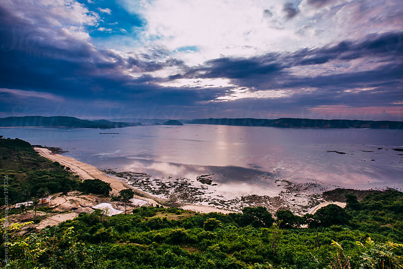 Ocean waves rolling in on rocky empty coast at sunrise. by Soren Egeberg for Stocksy United