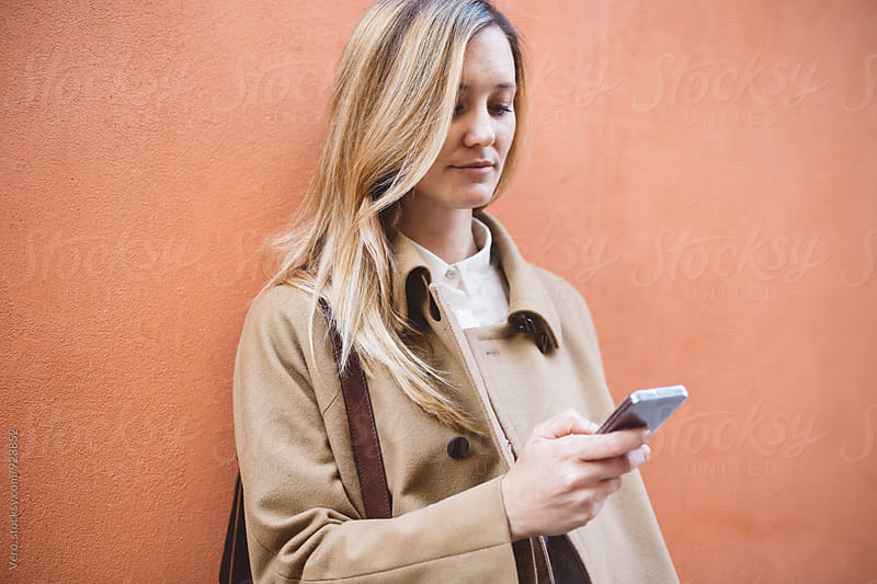 Blond woman in the city with a cell phone by Good Vibrations Images for Stocksy United