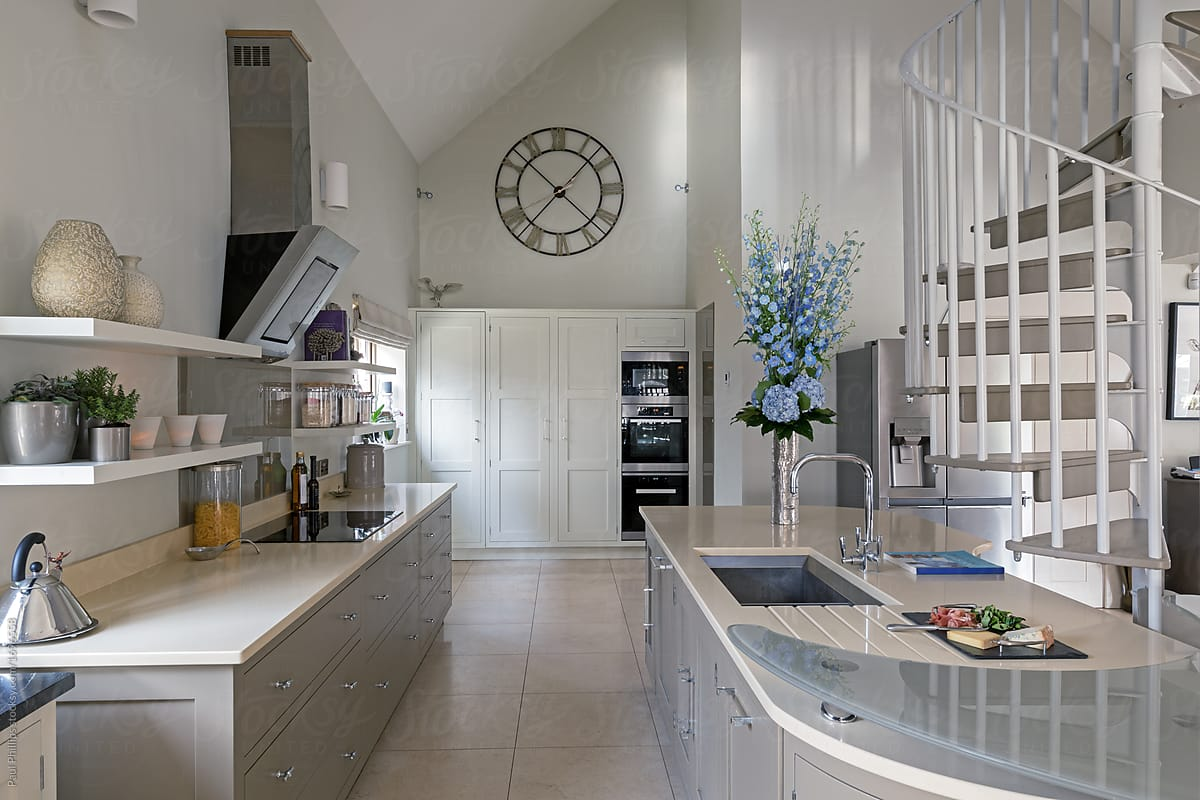 Modern kitchen area with spiral staircase leading to next level
