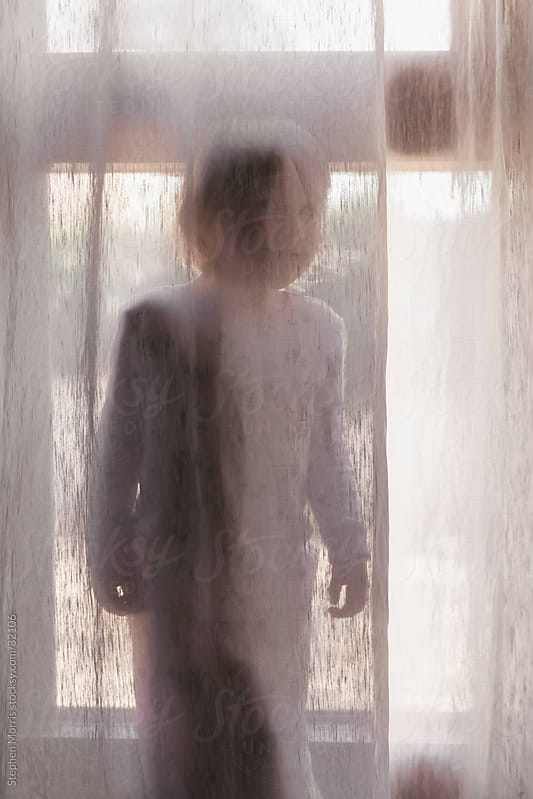Little Girl Hiding Behind Curtain by Stephen Morris for Stocksy United