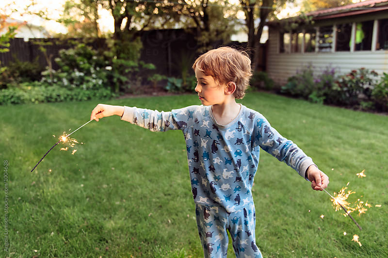 Small boy enjoying sparklers in the garden in the evening by Angela Lumsden for Stocksy United